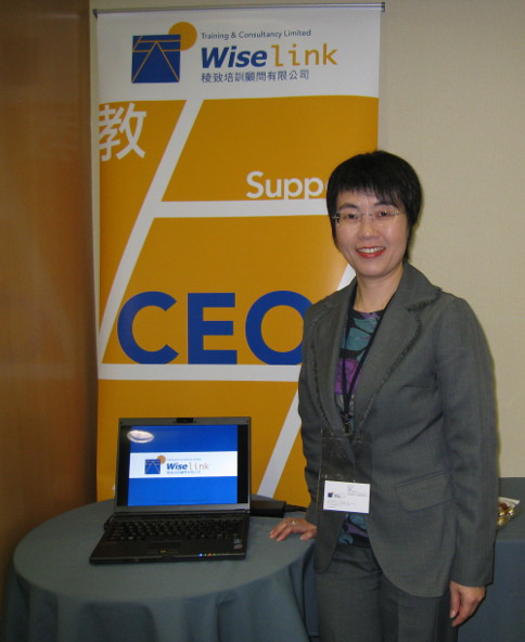 Maria Leung, Founder and Wise Coach, in front of a company display